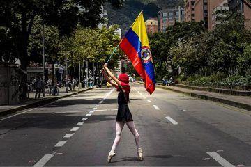Mujer con bandera colombiana. Revueltas en Colombia. Crónica y pensamiento crítico en Cultugrafía.